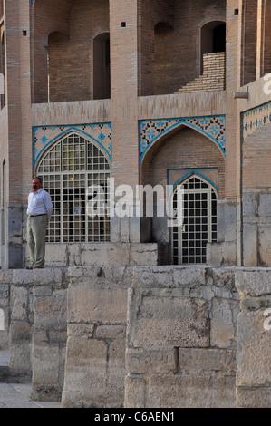An old man standing on the edge of Khaju Bridge, Isfahan Iran. - Stock Photo