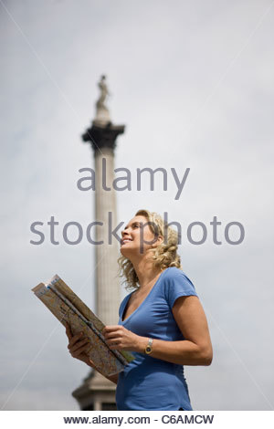A middle-aged woman standing in Trafalgar Square, looking at a map - Stock Photo