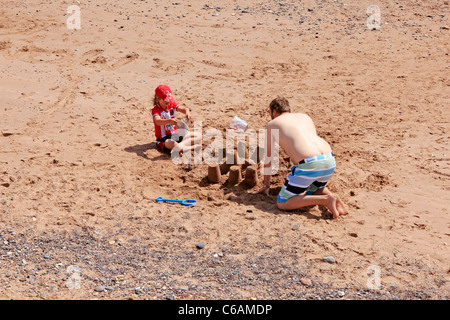 A father building sandcastles on the beach with his son in Devon England - Stock Photo