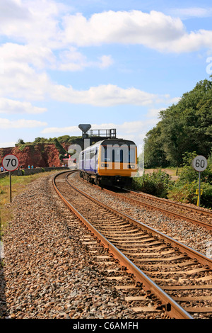 Small Commuter train on the Dawlish seafront railway line in Devon - Stock Photo