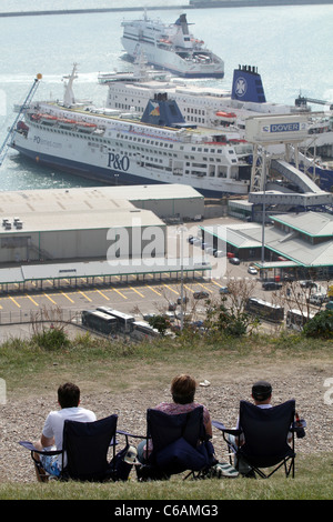 People sitting along the white cliffs of Dover coastal path with international sea ferry port in background. Kent, - Stock Photo