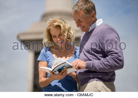 A middle-aged couple looking at a guidebook - Stock Photo