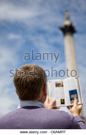 A middle-aged man in front of Nelson's column, looking at a guidebook - Stock Photo