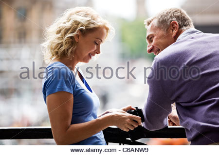 A middle-aged woman looking at photographs on her camera - Stock Photo