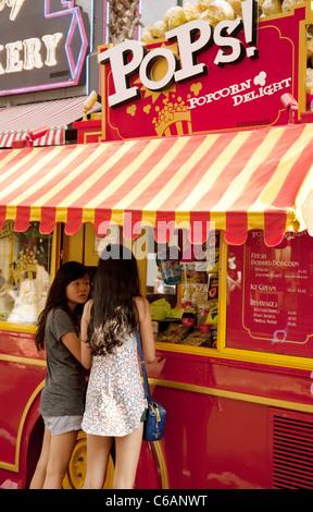 Two chinese girls buying popcorn, Universal Studios, Sentosa Island, Singapore - Stock Photo