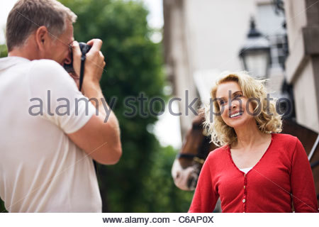 A middle-aged man taking a photograph of his partner in front of Horse Guards - Stock Photo