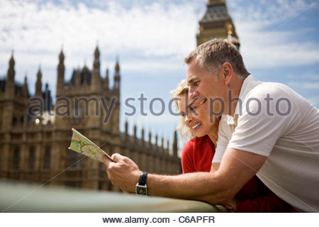A middle-aged couple standing near the Houses of Parliament, looking at a map - Stock Photo