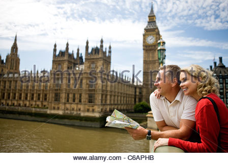 A middle-aged couple standing near the Houses of Parliament, looking along the river Thames - Stock Photo