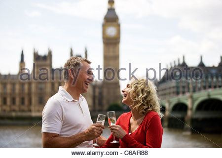 A middle-aged couple in front of the Houses of Parliament, drinking champagne - Stock Photo