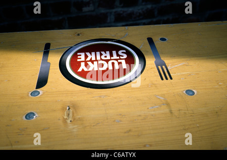 Lucky Strike tobacco ad on a beer garden table at Hafenbahnhof in Altona district of Hamburg. - Stock Photo