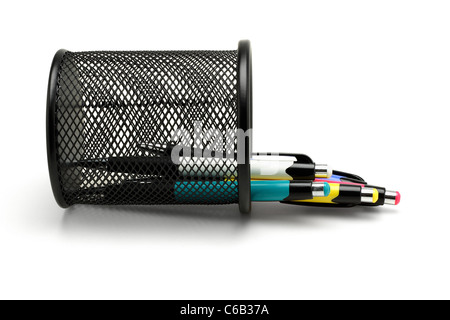 Multicolor ball point pens spilled out from fallen black basket container - Stock Photo