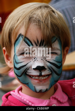 A young smiling girl with a painted face seen at a children's festival in Leipzig, Germany - Stock Photo