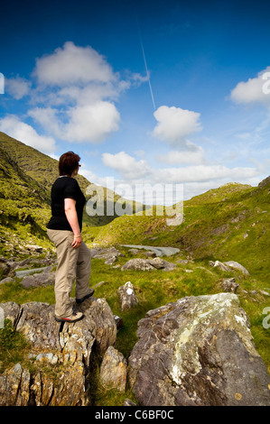 A female hiker looking at the landscape near the Ring of Kerry in Ireland - Stock Photo