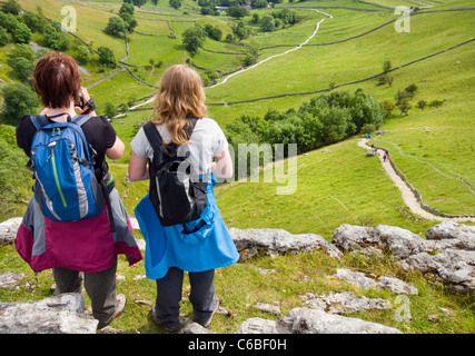 Hikers looking out from the top of the limestone pavement above Malham Cove in the Yorkshire Dales National Park, - Stock Photo