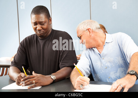 Older college student trying to copy off a younger student's test paper.  - Stock Photo
