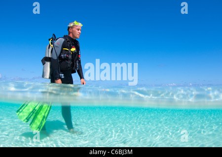 Split shot of scuba diver standing in clear waters in the shallows, North Huvadhoo Atoll, The Maldives - Stock Photo