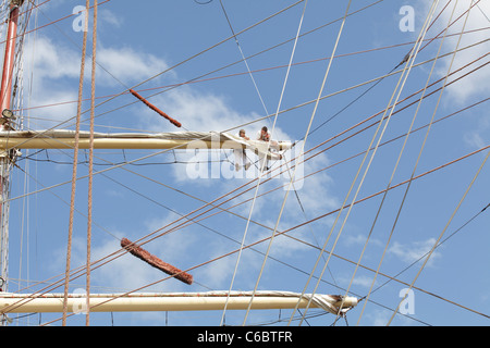 Crew working on the sails of a ship berthed at the Tall Ships Race 2011 in Greenock, Scotland, UK - Stock Photo