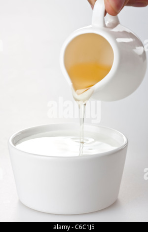 Honey Poured Into Yogurt - Stock Photo
