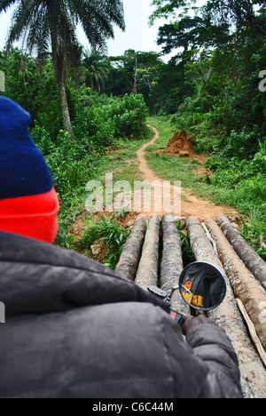 Motorbike crossing a flimsy log bridge on the track from Liberia (Lofa County) to Sierra Leone, West Africa - Stock Photo