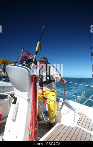 man at the helm of a sailing yacht in blue sky weather - Stock Photo