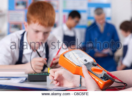 Students working on electronic device in vocational class together - Stock Photo