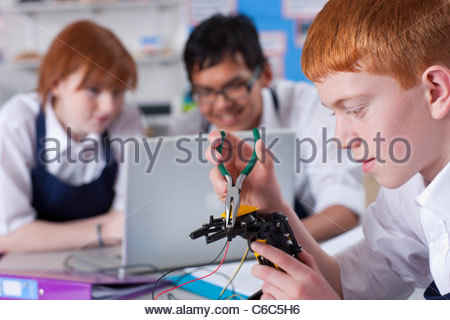 Students working on robotic device in vocational class together - Stock Photo