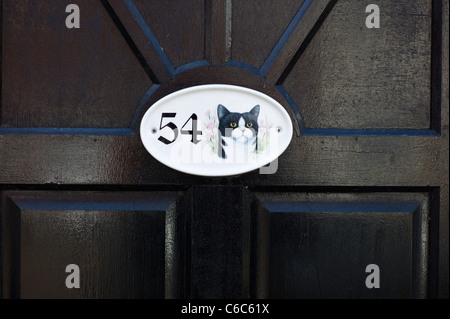 Small ceramic name plate featuring a cat on a front door - Stock Photo