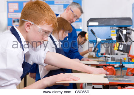 Students cutting wood in woodworking class - Stock Photo