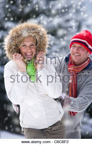Portrait of smiling couple in snowy woods - Stock Photo