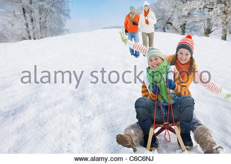 Family sledding down snowy hill - Stock Photo