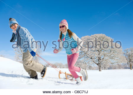 Smiling boy and girl pulling sled in sunny, snowy field - Stock Photo