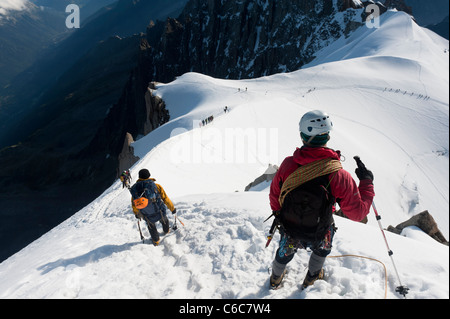 Climbers walking down the airy ridge of Aiguille du Midi at Chamonix, France - Stock Photo