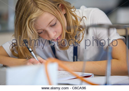 Close up of girl taking notes in science class - Stock Photo