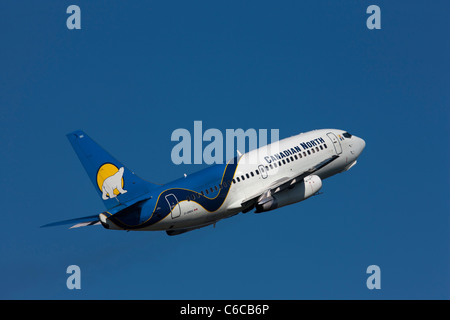 A Canadian North passenger jet aircraft sporting it's polar bear emblem takes off from Yellow Knife airport in Canada - Stock Photo