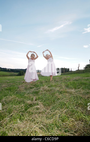 Girls running across a meadow in summer, Eyendorf, Lower Saxony, Germany, Europe - Stock Photo