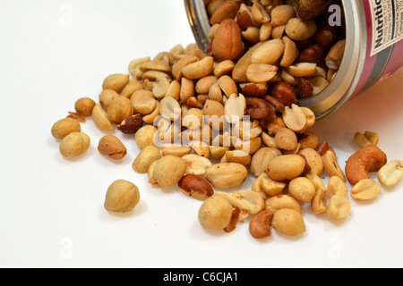 A open can of mixed nuts lays on it's side. - Stock Photo