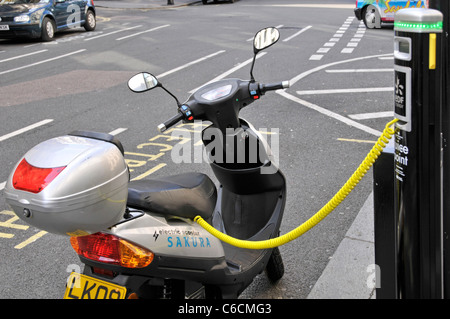 Electric car charging station & recharging parking bay occupied by scooter battery connected to electricity pillar - Stock Photo