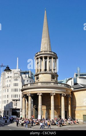 People sitting on steps of All Souls Church Langham Place designed by John Nash BBC Broadcasting House beyond in - Stock Photo