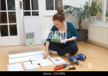 Young girl making a cabinet from a 'Flat Pack' DIY kit. - Stock Photo