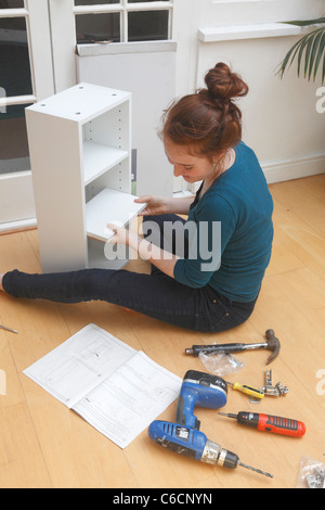 Teenage girl constructing a DIY cabinet - Stock Photo