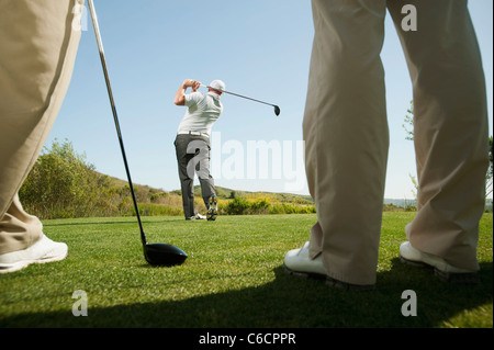 Men playing golf together on golf course - Stock Photo