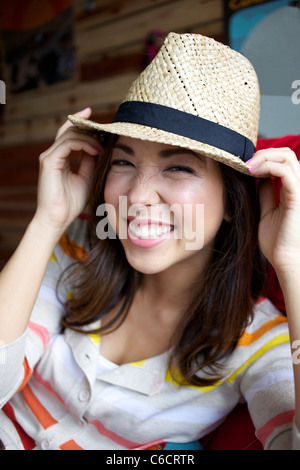 Smiling mixed race woman wearing hat