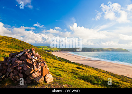 Evening light on the cairn on Potter's Hill overlooking Woolacombe and Putsborough Sands towards Baggy Point, Devon, - Stock Photo