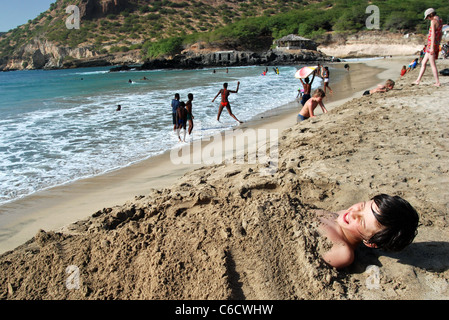A boy covered in sand on the Tarrafal beach of Santiago Island, Cape Verde - Stock Photo