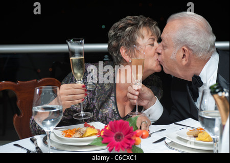 Kissing Hispanic couple toasting with Champagne in restaurant - Stock Photo