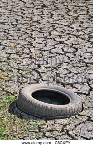 Old tyre in a dry river. Environmental and ecology problem - Stock Photo