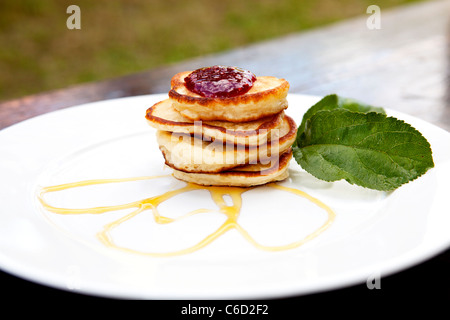 Pancakes On A Plate Covered With Jam And Maple Syrup With Mint On The Side - Stock Photo