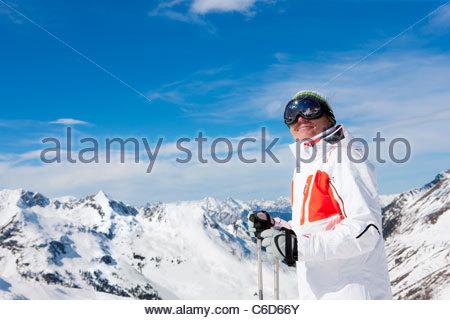 Smiling man wearing ski goggles and holding ski poles on snowy mountain - Stock Photo