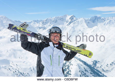Portrait of smiling senior man with skis on snowy mountain top - Stock Photo