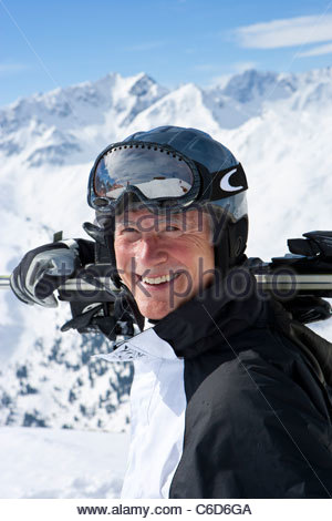 Close up portrait of smiling senior man with skis on snowy mountain top - Stock Photo
